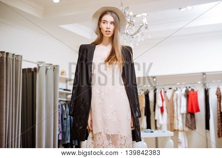 Closeup of gorgeous young woman in dress, jacket and hat standing in clothig store