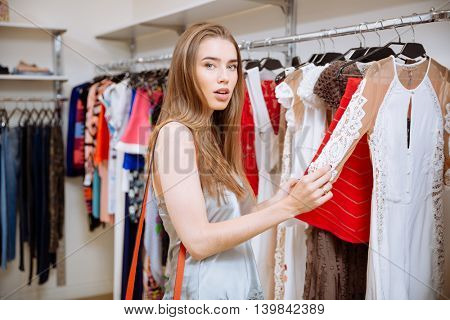 Cute young woman doing shopping and choosing dress in clothing store