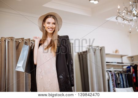 Smiling stylish young woman in hat holding shopping bags in the shop