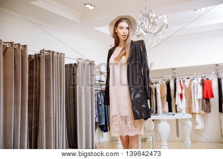 Portrait of attractive young woman in hat standing in clothing shop