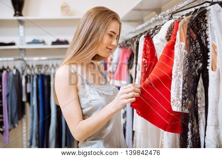 Beautiful young woman doing shopping and choosing clothes in shop