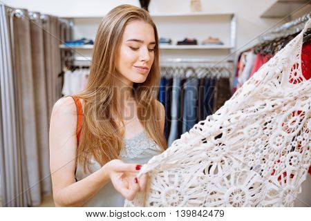 Pensive young woman thinking and choosing dress in the shop