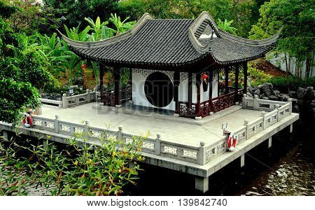 Hong Kong China - December 20 2007: Lakeside Lung Nam Pavilion with terrace moon gate and flying eave roofs in Kowloon Walled City Park