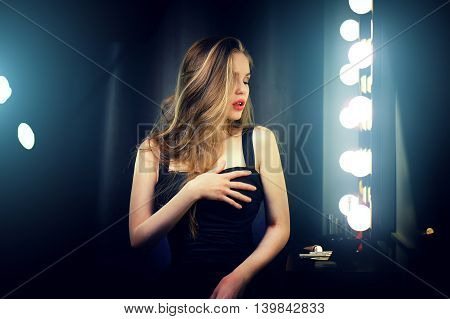 Beautiful sexy young caucasian woman in black dress sensual backstage dramatic shot.