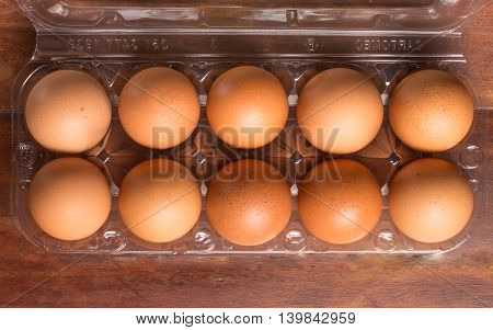 Transparent Egg Box over a wooden table