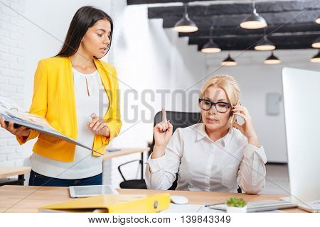 Two smart businesswomen discussing ideas at the table in the office