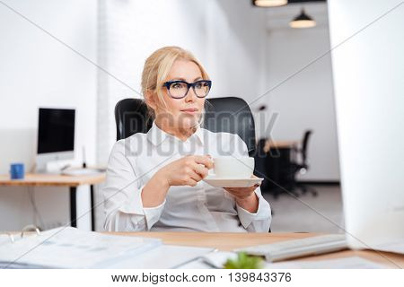 Mature businesswoman drinking coffee with pc computer at office