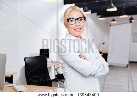 Portrait of a cheerful mature business woman standing with arms folded in office