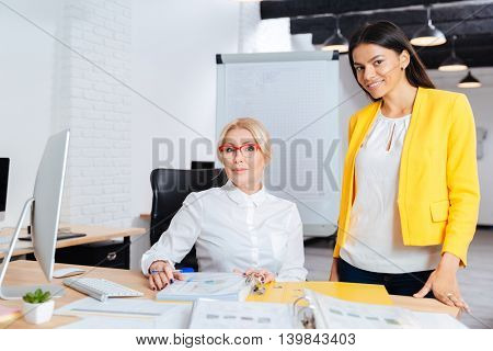 Two smiling businesswomen working together on the computer at the table in office