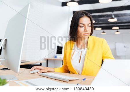 Portrait of a serious beautiful businesswoman using laptop in office