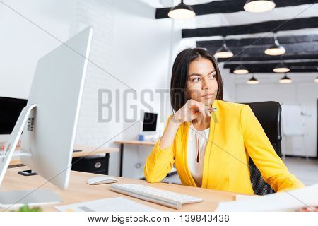 Portrait of a serious young businesswoman looking away in office