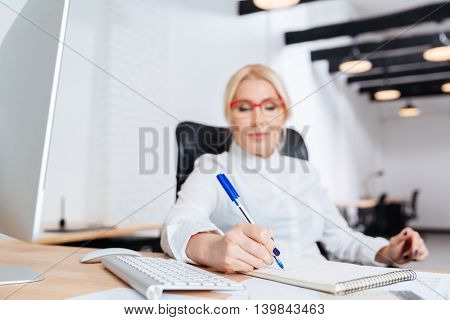 Portrait of a smiling attractive mature businesswoman writing in notebook in the office