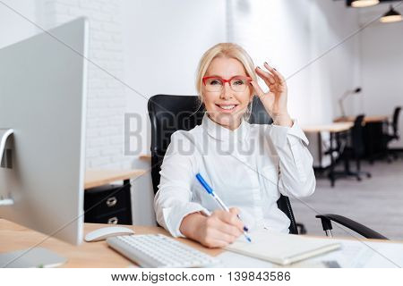 Portrait of a smiling attractive mature businesswoman using laptop in office