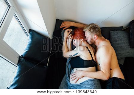 Pregnant woman and man lying on a bed in the bedroom