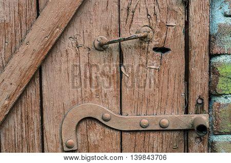Vintage wooden door closeup with a handle and locking mechanism