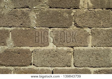Old wall built of concrete blocks. It has many cracks