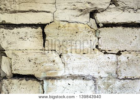 Aged brick wall with cracks. It is covered with plaster