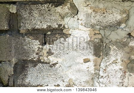 Aged brick wall with parts of it covered with aged plaster