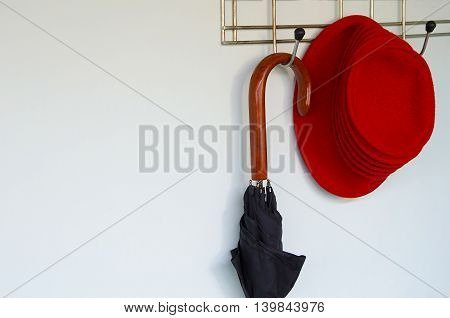 Umbrella with a fashionable red hat on a hanger against a wall