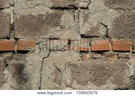 Aged wall made of bricks and concrete blocks