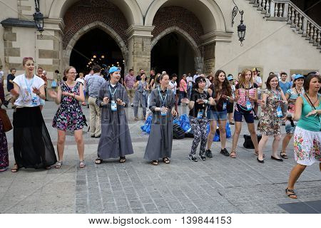 CRACOW POLAND - JULY 24 2016: Pilgrims of World Youth Day sing and dance on the Main Square in Cracow. Poland