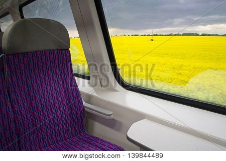 Stormy skies and fields of blossoming rapeseed outside the train