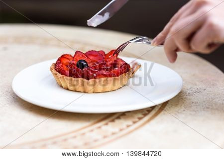 Photo of female hands cutting a fruit cake with strawberries mint and blackcurrant on a white plate on a restaurant table.