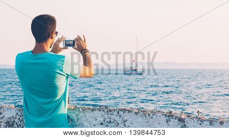 Back view of a young man tourist taking photo of yacht with smartphone in front sea