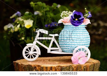 Photo of a white bicycle with purple and pink flowers on baggage on a tree stump.