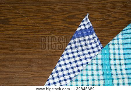 Two checkered napkins on a wooden table