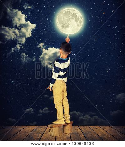 boy pulls out his finger to the moon