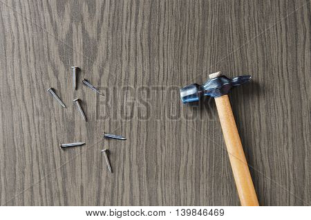 Hammer with nails on a wooden background