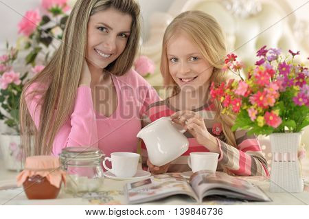 Smiling mother with little daughter drinking  tea with magazine at kitchen