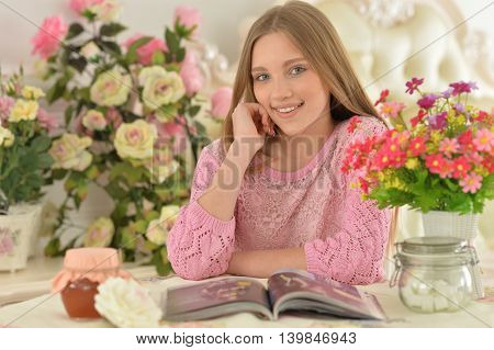 Beautiful  teenager girl reading magazine at home