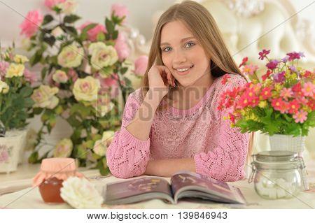 Beautiful  teenager girl reading magazine at home