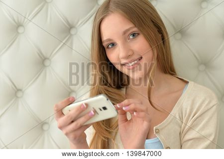 Portrait of a cute teenager girl using modern smartphone