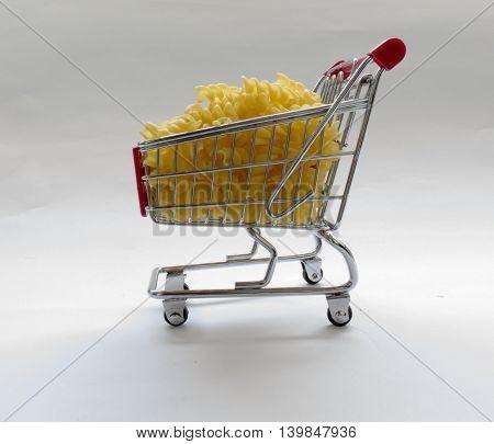 Shopping cart filled with macaroni pasta on white