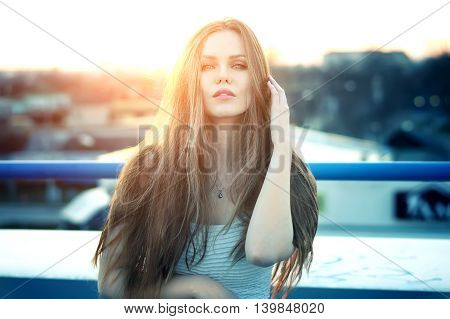 Outdoor portrait of young pretty sexy woman with sensual lips posing at roof at the end of bright sunset. Lovely soft back light.