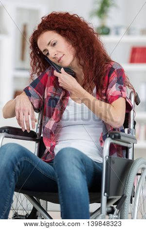 cheerful disabled redhead woman talking on cell phone