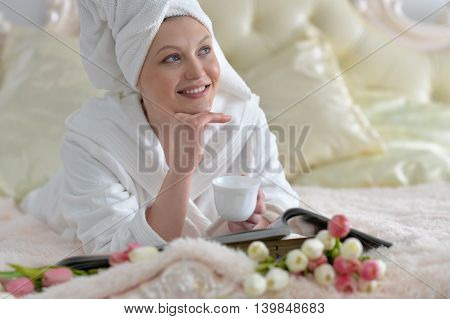 beautiful young woman wearing a white bathrobe and drinking tea at home