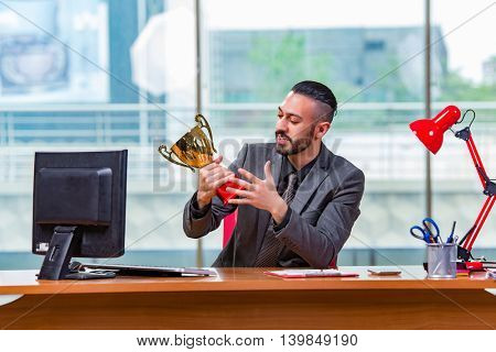 Businessman winning cup trophy in the office