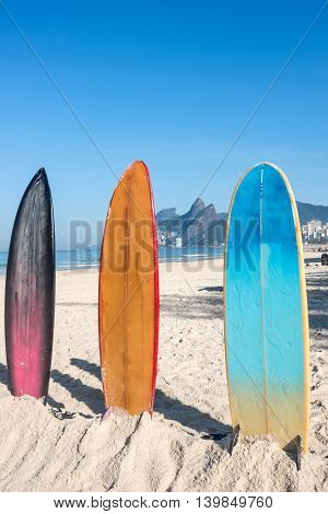 Surfboards standing upright in bright sun on the Ipanema beach Rio de Janeiro Brazil