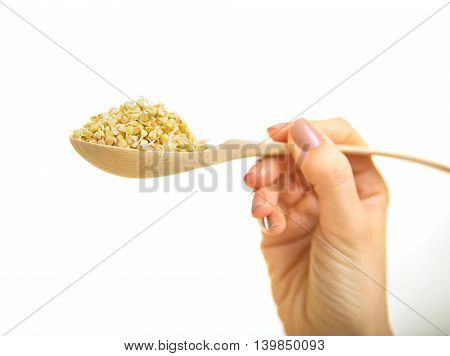 Fresh Green Sprouts Buckwheat in the spoon Closeup. Female hand holding Spoon with Sprouts Buckwheat white background. Raw Healthy Organic Diet. Healthy Vegetarian Eco Food concept Dieting