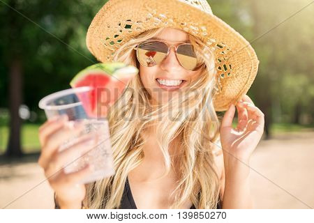A photo of young beautiful woman in panama hat. She's holding a cup of drink and smiling happily.