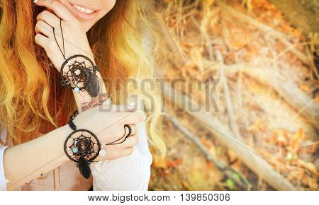 Handcrafted bracelets on a woman hands, dreamcatcher jewelry, close up, boho chic style, sunny autumn outdoor, soft colors, copy space for text