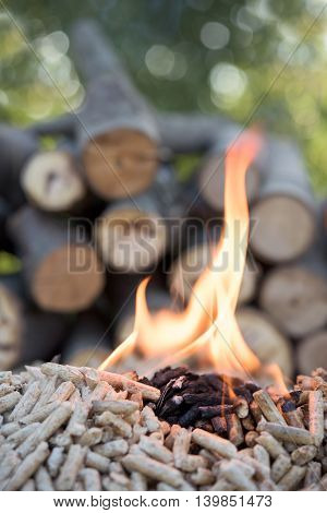 Oak pellets in flames infront pile of wood