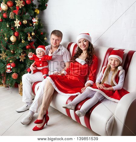 Happy family dressed in Santa costumes celebrating the New Year and Christmas.