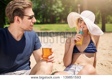 A photo of young man flirting with beautiful woman on the beach.