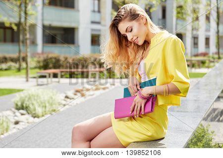 Beautiful young woman in yellow dress posing outdoors, street fashion