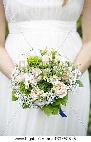bride in white dress with wedding bouquet in hands